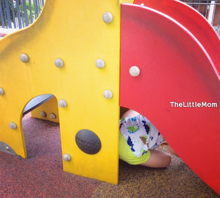 I think the boy likes the playground cause he get to hide under it. How many playgrounds now allow you to do that?